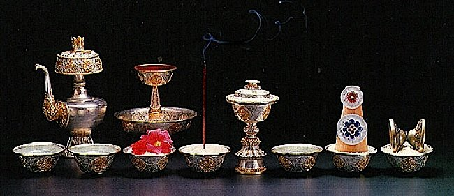 The eight sensory offerings from left to right are: water for drinking, water for washing (the feet), flowers for beauty, incense for smell, light (candles, buttlerlamps or light) for seeing, perfumes, food for eating, and sound or music for listening.