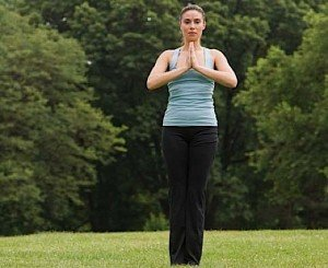 Woman standing in meditation with hands held in prayer