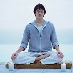 A man in lotus posture meditating on a dock.