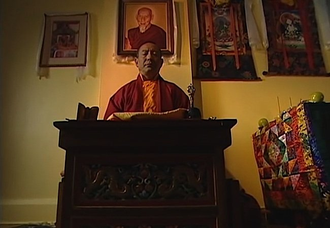 Zasep Tulku Rinpoche meditating. Behind him is a portrait of another of his great teachers, Zong Rinpoche.