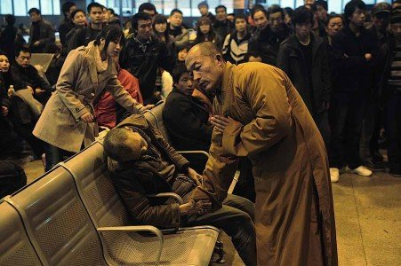A monk holds the hand of a deceased person found on a train platform in China.