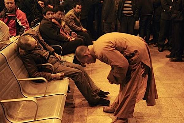 The humble actions of a monk at a train station in China captivated the world. The monk bows to the deceased in respect. He holds his hand to comfort him (feature picture top).