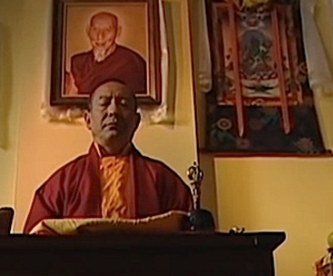 """A still frame from the movie """"Come Again"""" featuring Zasep Rinpoche. Behind him is a portrait of his guru H.H. Zong Rinpoche."""