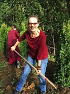 Lama Acharya Dr. Shannon Young planting a tree at a retreat centre.