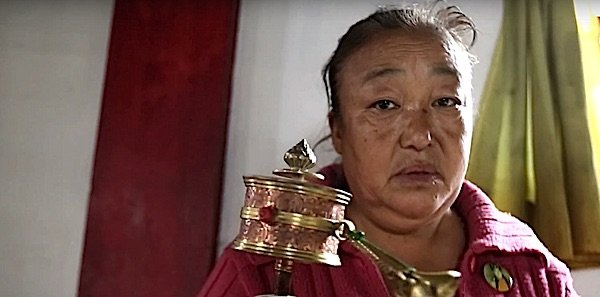 Buddha Weekly Lady spins prayerr wheel Buddhism