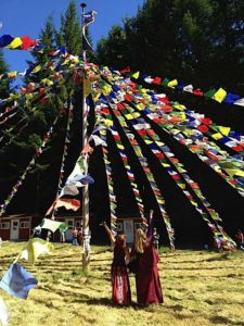 Buddha Weekly Lama Dr. Shannon Young teaching at a retreat with prayer flags Buddhism
