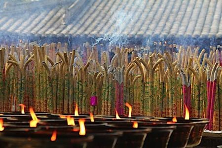 Buddha Weekly light and incense candles and joss sticks at Buddhist temple Buddhism
