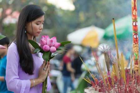 Flower and joss stick offerings to Buddha at temple