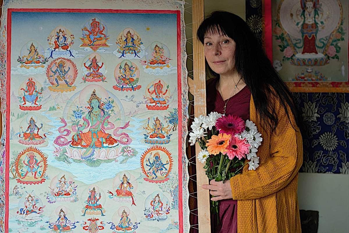 Buddha Weekly Artist angeli Lhadripa Shkonda posing beside her Thangka masterpiece of 21 Taras Surya Gupta Buddhism