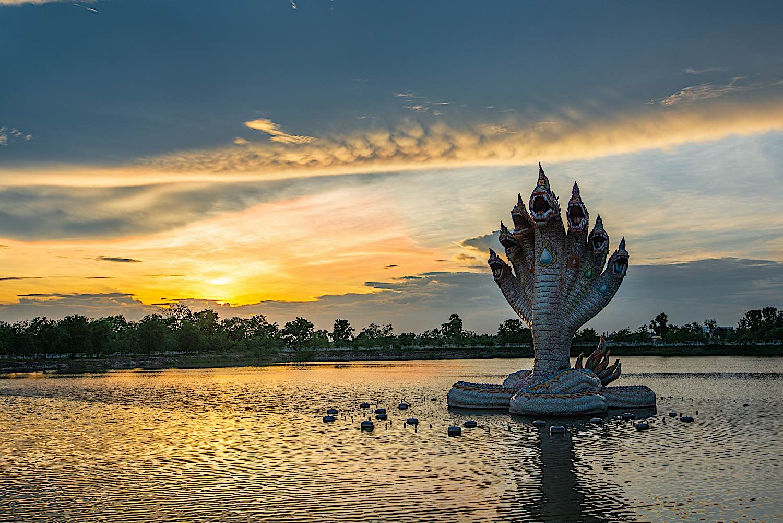 Beautiful Naga statue at sunset, rising up out of the water, in Wat Ban Rai Buddhist Temple Nakhonratchasima Thailand.