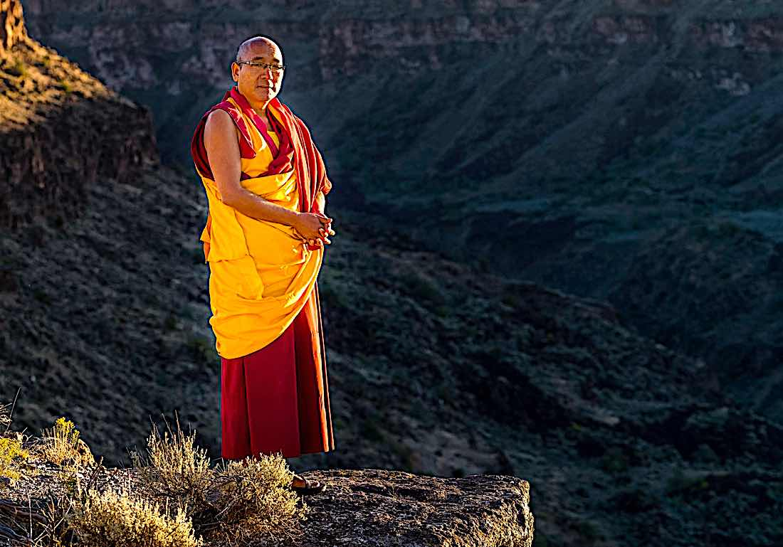 Buddha Weekly Geshe Sherab on cliff in mountains Buddhism
