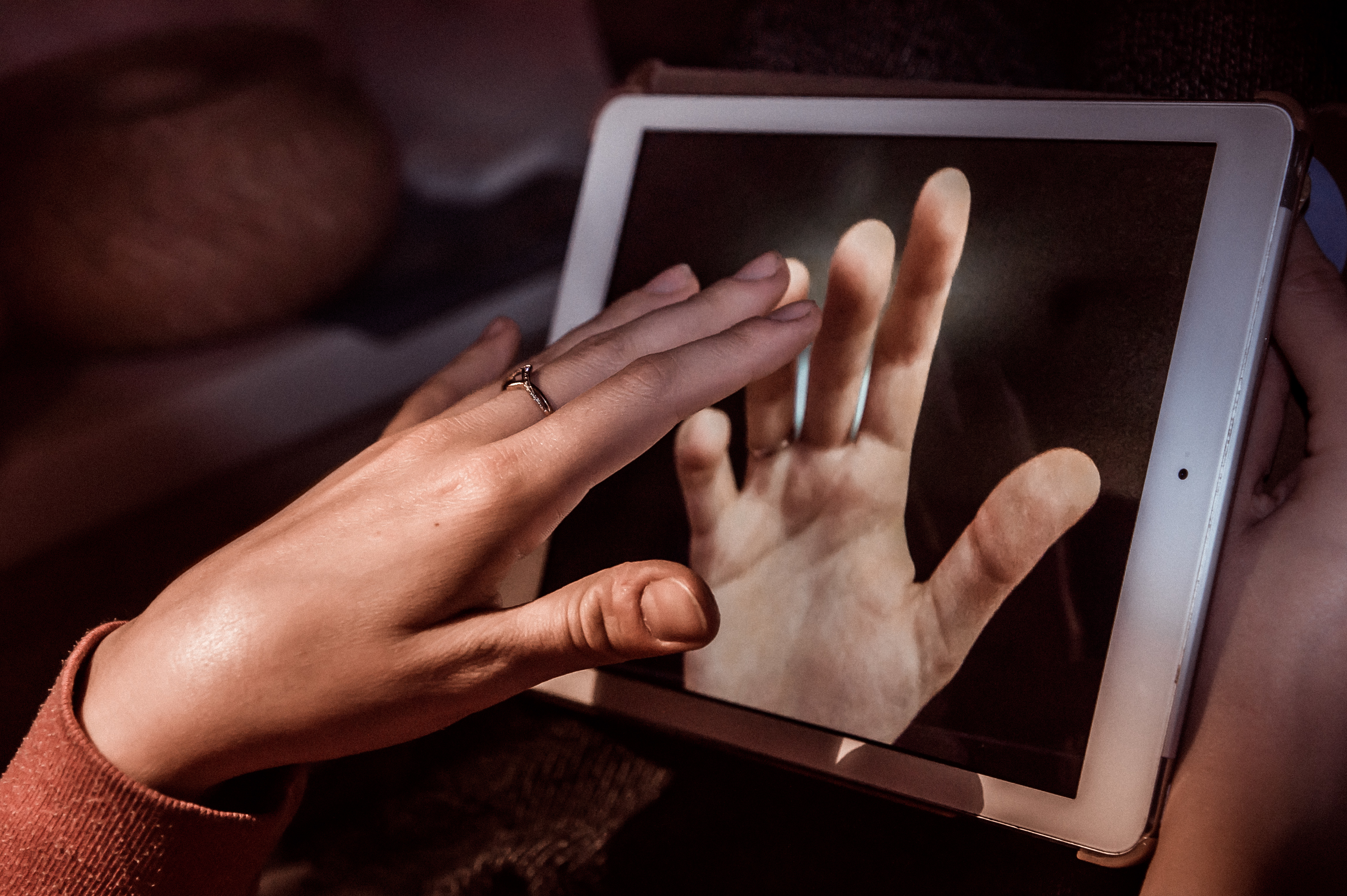 Long distance relationship hands touching through ipad