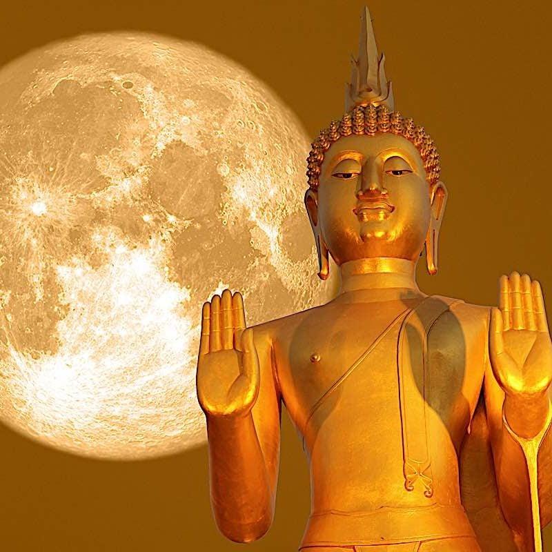 Buddha statue against a full moon.