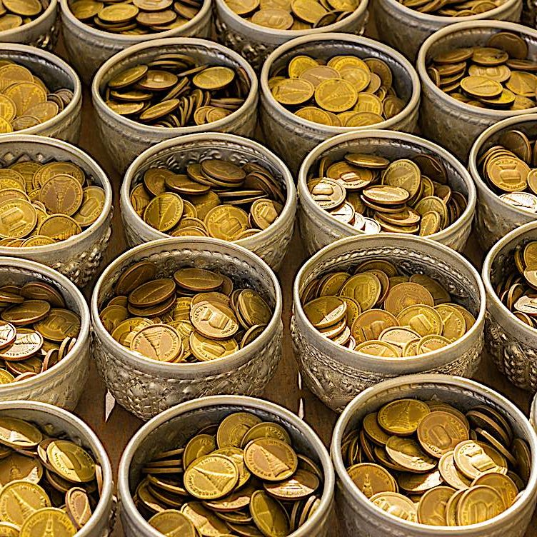 Traditional offering bowls in Thailand temple, where golden coins fill each bowl. Wealth itself is not a negative in Buddhism, but the wealth has to be righteously obtained and righteously used.