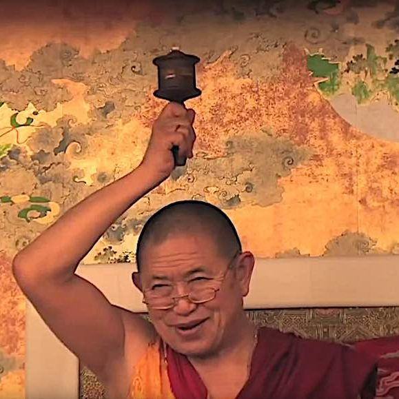 Garchen Rinpoche with his famous prayer wheel. The prayer wheel is typically filled wih millions of written mantras, usually the compassion mantra, or Mani Mantra, Om Mani Padme Hum. The compassion of Garchen Rinpoche is world-renowned.
