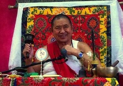 H.E. Garchen Rinpoche teaching with spinning prayer wheel in right hand.