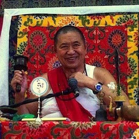 H.E. Garchen Rinpoche teaching with spinning prayer wheel in right hand.