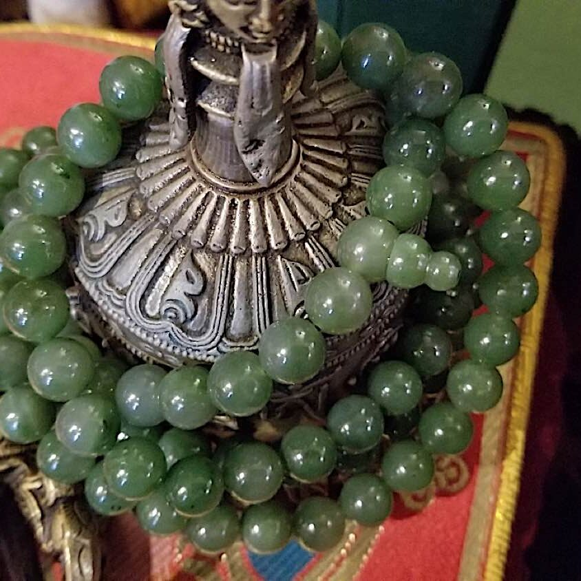 A green jade mantra consecrated to Green Tara wrapped around dorje and bell on the altar.