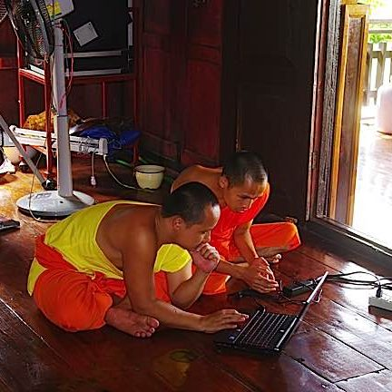 Buddhist monks in Thailand using a computer on the floor of the temple. Computers, mobile phones and tablets are common today in temples and monasteries.