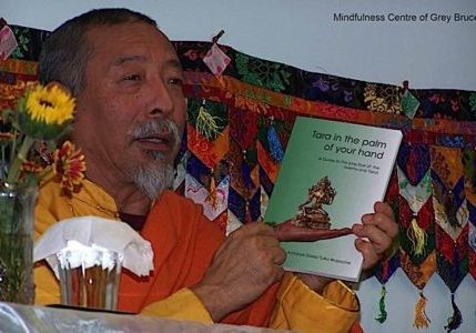 Venerable Zasep Rinpoche teaching at a Tara weekend using the commentary book, Tara in the Palm of Your Hand, as a reference.