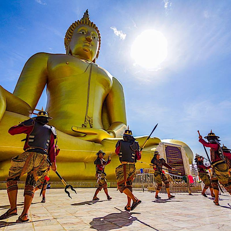 Angthong, Thailand - July 15, 2014: Actors performing fighting in ancient warrior style in front of large golden Buddha Image to celebrate Buddhist event at Wat Muang, Buddhist temple in Angthong, Thailand.