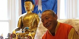 Buddha Weekly Zasep Tulku Rinpoche laughing at Gaden Choling in front of altar Buddhism custom crop