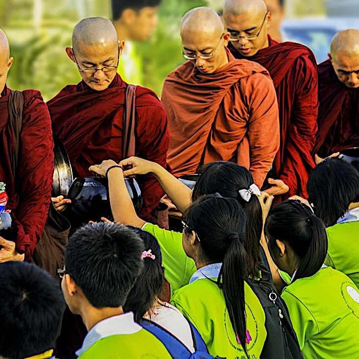 """Youth give """"dana"""" to monastic Sangha, a meritorious action."""
