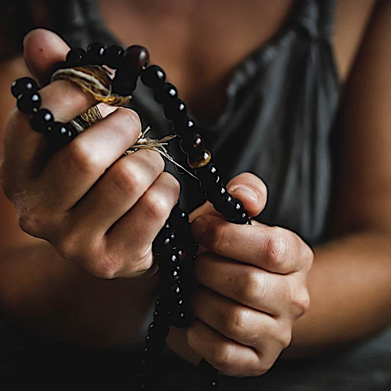 Photo of a hand holding a Mala, by Chelsea shapouri on Unsplash